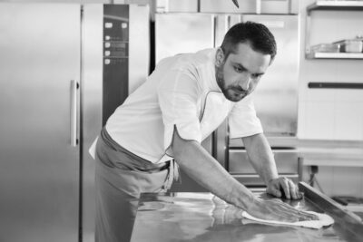 When preparing foods keep it clean, a dirty area should not be seen. Young male professional cook cleaning in commercial kitchen